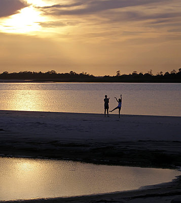 Silhoutted figures on the beach at sunset. - p1072m874560f by Joseph Shields