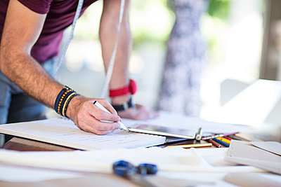 Close-up of fashion designer taking notes on table - p300m1581440 by zerocreatives