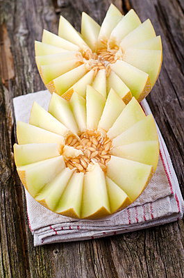 Honeydew melon with napkin on wooden table;  close up - p300m836991f by Doris.H