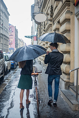 Couple with umbrella on morning commute, Budapest, Hungary - p429m2019483 by Seb Oliver