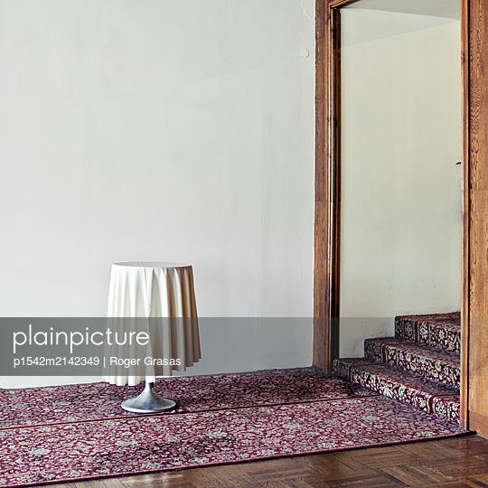 High table on a carpet next to staircase