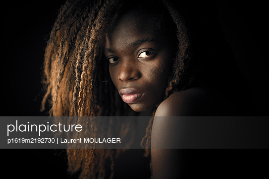 Portrait of a young woman looking at the camera behind her shoulder - p1619m2192730 by Laurent MOULAGER