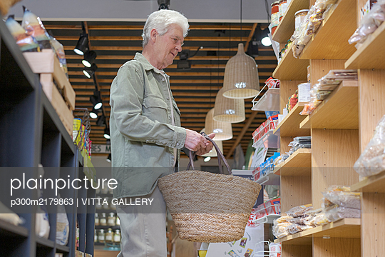 Senior man shopping in a small store - p300m2179863 by VITTA GALLERY