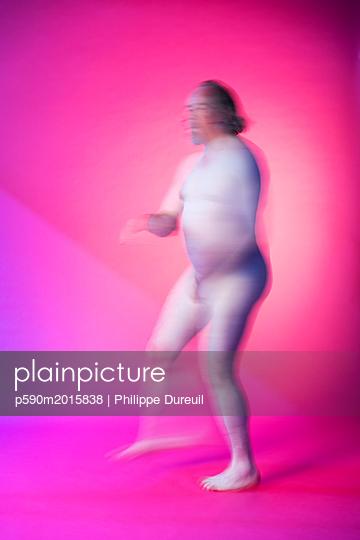 Nackter Mann tanzt vor einem rosa Hintergrund - p590m2015838 von Philippe Dureuil