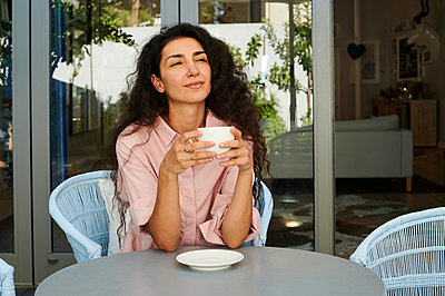 Woman with coffee cup on the terrace, portrait - p1640m2254623 by Holly & John