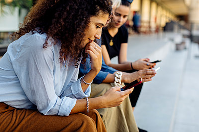 Three women sitting on steps in a row, using smartphones - p300m2156688 by Sofie Delauw