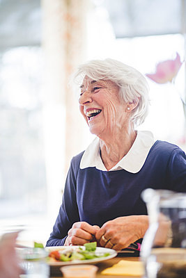 Cheerful senior woman having lunch at table in nursing home - p426m2018568 by Maskot