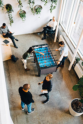 Male and female colleagues playing foosball while taking break from work in office - p426m2259452 by Maskot
