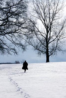 Man  walking in snow - p476m894095 by Ilona Wellmann