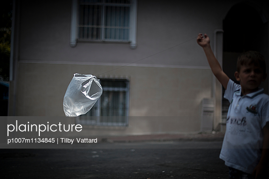 Boy playing with flying plastic bag in sun light - p1007m1134845 by Tilby Vattard