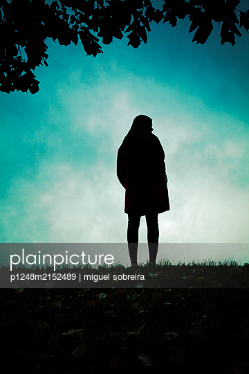 Silhouette of a woman on a hill - p1248m2152489 by miguel sobreira