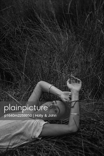 Young woman lying in grass - p1640m2259950 by Holly & John