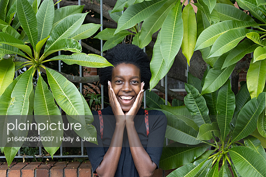 African woman between green leaves, portrait - p1640m2260037 by Holly & John