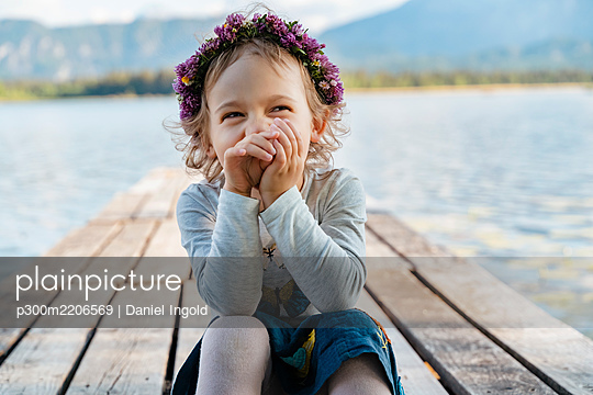 Close-up of cute girl wearing tiara laughing while sitting on jetty against lake - p300m2206569 by Daniel Ingold