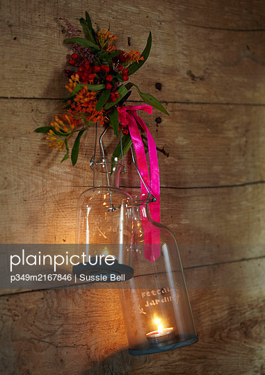Glass candle holders hang with pink ribbon in rustic wood cabin  Autumn  UK - p349m2167846 by Sussie Bell