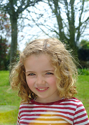 Little blond girl smiling in red stripes pullover - p1096m1219031 by Rajkumar Singh