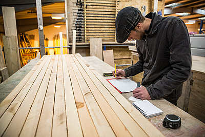 Man wearing flat cap standing at a workbench with wooden planks in a warehouse, holding ruler, writing measurements on piece of paper. - p1100m1575731 by Mint Images