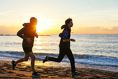 Father and son jogging at beach against sea during sunset - p1166m1508181 by Cavan Images