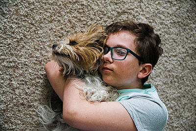 Tween together with his pet lying on the floor in the living room. - p1166m2107771 by Cavan Images