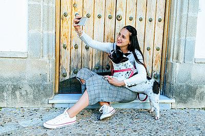 Young woman using smartphone, taking a selfie with her dog - p300m2012703 von Kiko Jimenez