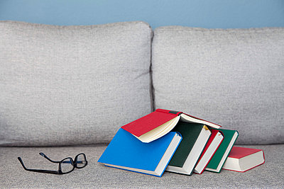 Stack of books on a sofa - p4540855 by Lubitz + Dorner