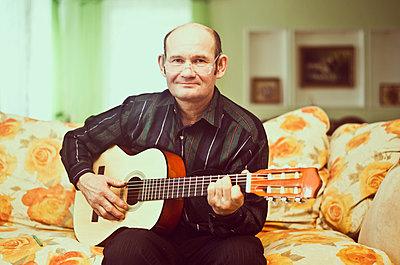 Caucasian man playing guitar on sofa - p555m1412363 by Aleksander Rubtsov