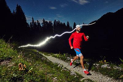 Mann beim Trail Running in der Nacht - p913m1113046 von LPF