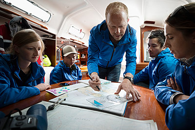 Sailing team plotting course at map on sailboat - p1192m1583230 by Hero Images