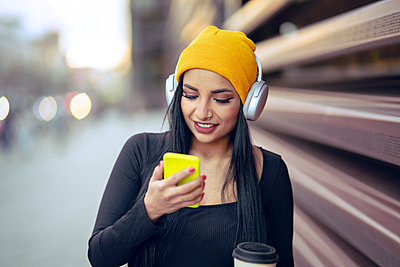 Young beautiful woman listening music over headphones while using smart phone at street - p300m2252075 by Jose Carlos Ichiro