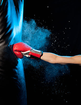Cropped image of man hitting punching bag against black background - p301m1482546 by Benne Ochs
