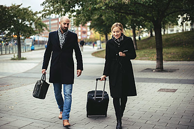 Full length of business people with luggage walking on sidewalk - p426m1407098 by Maskot
