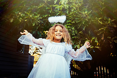 Mixed race girl wearing angel costume in backyard - p555m1412569 by Inti St Clair