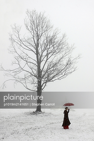 Woman with umbrella in snow - p1019m2141651 by Stephen Carroll