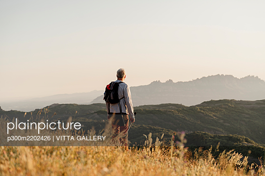 Active senior man with backpack looking at mountain range during sunset - p300m2202426 by VITTA GALLERY