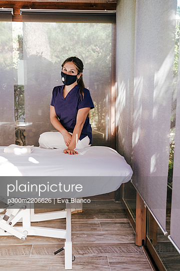 Female therapist wearing mask standing by massage table in spa - p300m2206626 by Eva Blanco