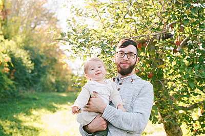a proud father and his 6 month old daughter next to an apple tree. - p1166m2171975 by Cavan Images
