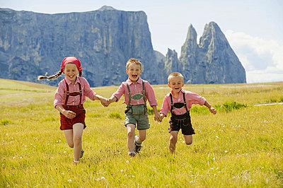 Italy, Seiseralm, Three children (4-5), (6-7), (8-9) running in field - p3008840f by Westend61