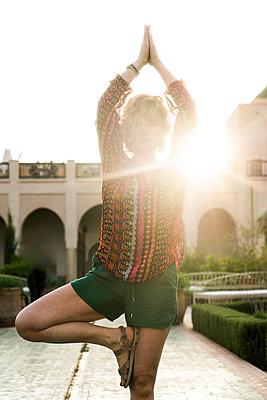 Morocco, Marrakesh, tourist doing yoga in courtyard - p300m1449270 by Kike Arnaiz