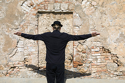 Rear view of man wearing a bowler hat standing at stone wall with arms outstretched - p300m2104400 by Petra Stockhausen