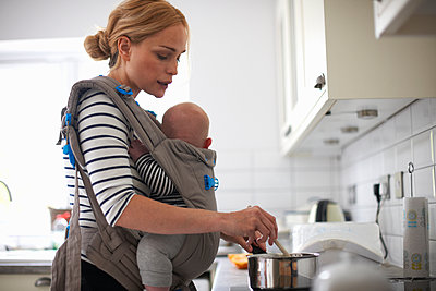 Woman cooking in kitchen, baby strapped to body in sling - p429m1469234 by Peter Muller