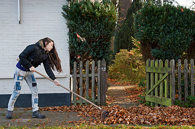 Teenager sweeping leaves - p896m834948 by Sabine Joosten