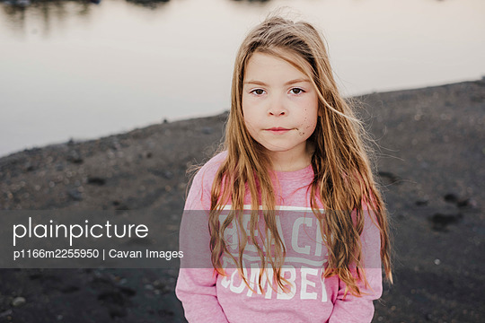 Young girl standing on black sand at the beach during dusk - p1166m2255950 by Cavan Images
