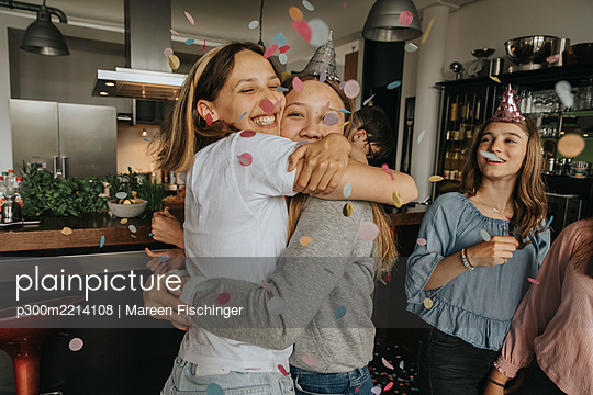 Happy friends embracing while standing amidst confetti in birthday party at home - p300m2214108 by Mareen Fischinger