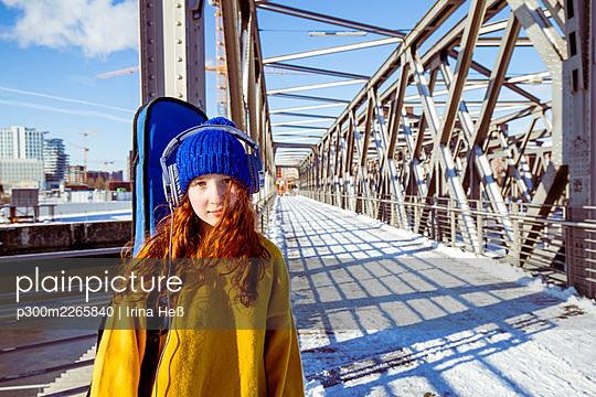 Girl with guitar listening music through headphones while standing on bridge - p300m2265840 by Irina Heß