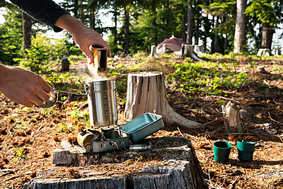 Cropped image of man pouring food in container over camping stove in forest - p1166m1163585 by Cavan Images