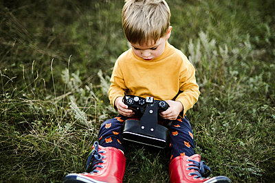 Boy  with camera while sitting on grassy field - p1166m2096001 by Cavan Images