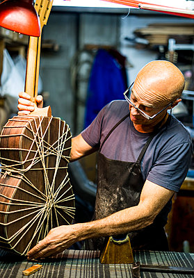 Luthier man making guitars in artisan workshop in Spain. - p1166m2129683 by Cavan Images