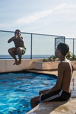 Two boys having fun in swimming pool - p300m1140747 by Mauro Grigollo