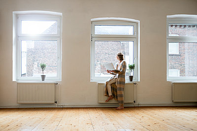 Mature woman in empty room holding laptop at the window - p300m1562744 by Robijn Page