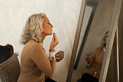 Profile of mature businesswoman applying makeup - p300m2102896 by Francesco Buttitta